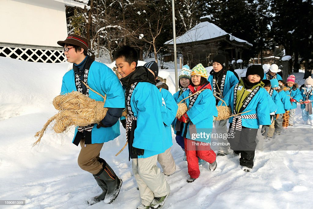 School pupils holding a 7-meter-long, 30-kilogram straw snake walk around the town during the Hebi-no-Gonenshi, or Snake's New Year on January 7, 2013 in Aizumisato, Fukushima, Japan. The event, has more than 120 years tradition, started in Meiji Period when local people suffered from water shortage prayed to a straw snake.