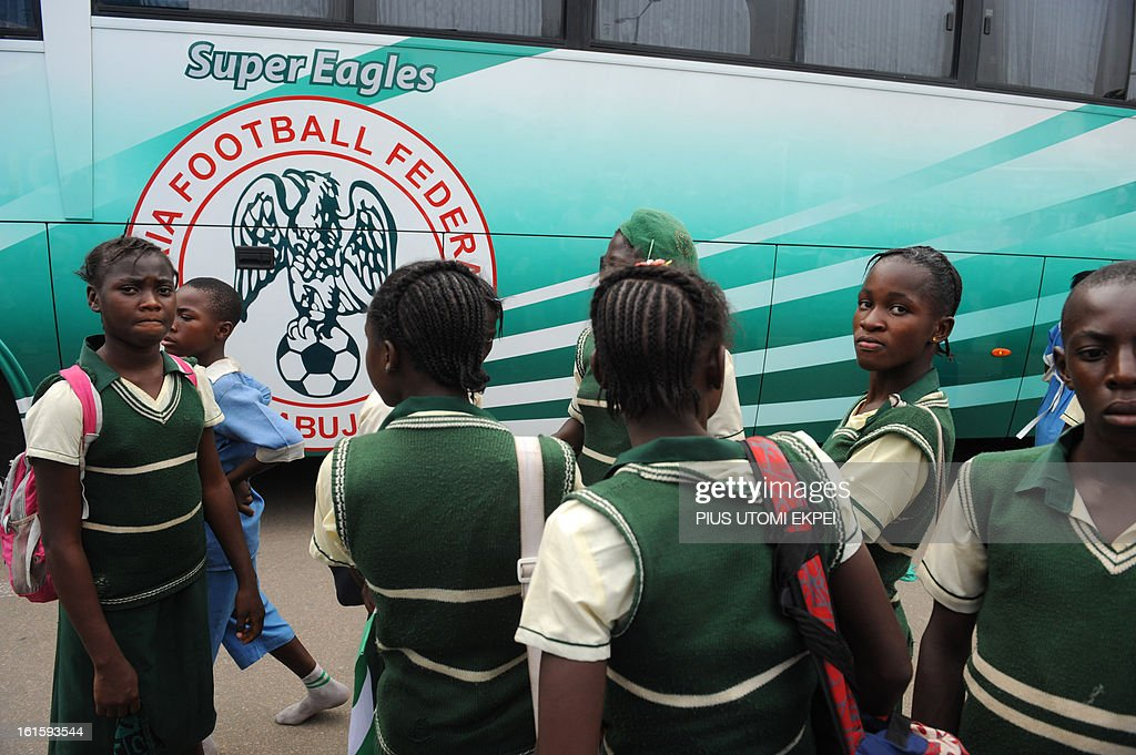 School pupils in their uniforms arrive to welcome the Nigerian football team at the airport in Abuja on February 12, 2013. The newly crowned African champions Nigerian Super Eagles arrives in Abuja to a warm reception by fans and government officials after defeating Burkina Faso to win the 2013 African Cup of Nations in South Africa. AFP PHOTO/PIUS UTOMI EKPEI