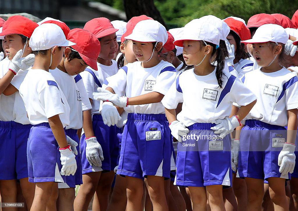 School pupils wearing cotton gloves to avoid the possible radiation exposure from the ground attend their sports meet at Meitoku Primary School on September 17, 2011 in Kitaibaraki, Ibaraki, Japan. The school is located 80km southeast from the troubled Fukushima Daiichi Nuclear Power Plant.