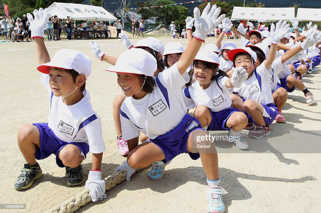 School pupils wearing cotton gloves to avoid the possible radiation exposure from the ground participate in the tug-of war during their sports meet at Meitoku Primary School on September 17, 2011 in Kitaibaraki, Ibaraki, Japan. The school is located 80km southeast from the troubled Fukushima Daiichi Nuclear Power Plant.