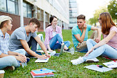 Teenage groupmats sitting on lawn of campus and carrying out homework