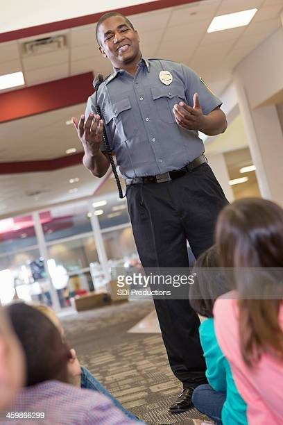 School security or police officer teaching safety procedures to students