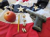 school shootings & gun control debate symbolized by an apple, pencil, bullets, gun on a US flag bunting