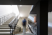 One person walking down stairs in motion effect photography inside building.