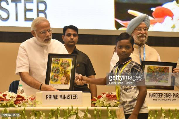A school student presents the painting to Prime Minister Narendra Modi during the 3rd anniversary of Swachh Bharat Mission and the conclusion of...