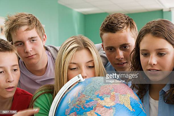School students looking at a globe