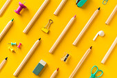 Diagonally arranged school supplies and coloring pencils  on yellow background. Back to school colorful flat lay