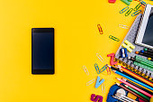 School supplies and mobile phone on yellow background