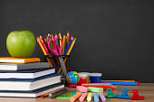Stack of books and school supplies in front of a black chalkboard