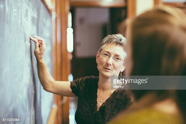 School teacher at chalkboard explaining math teenage student