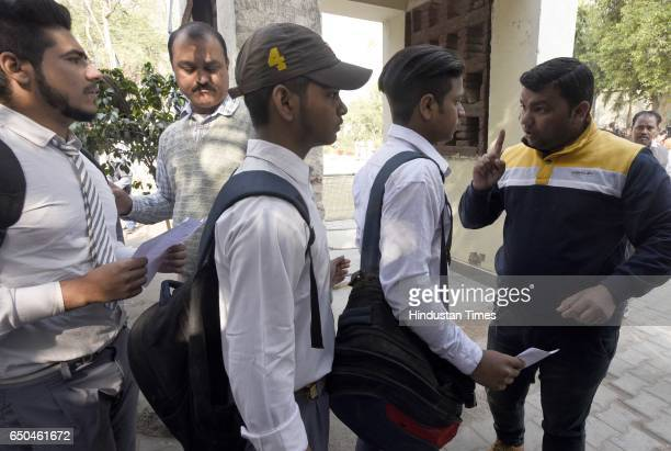 School teacher check Students enter for the 12th class English as board exams at Govt girls senior secondary school on March 9 2017 in New Delhi...