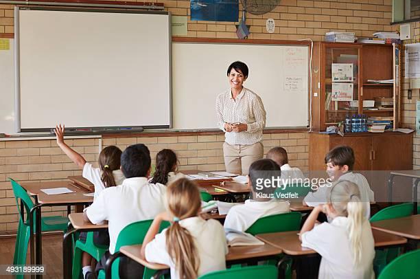 School teacher in classroom with kids