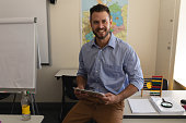 Happy school teacher with digital tablet looking at camera and sitting on desk in classroom