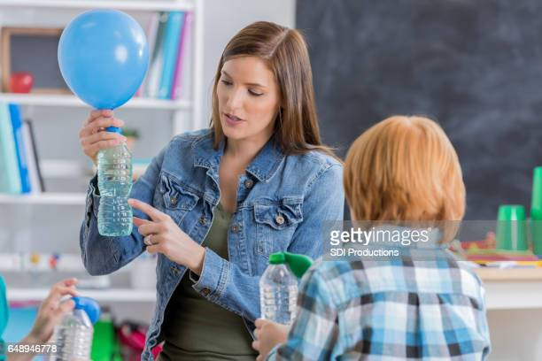 School teacher uses a bottle and balloon during science experiment