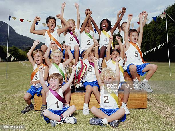 School team (4-11) sitting with trophies in sports field, cheering