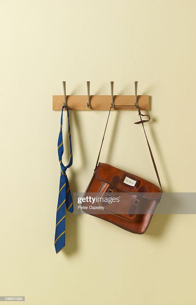 School tie and satchel on coat rack