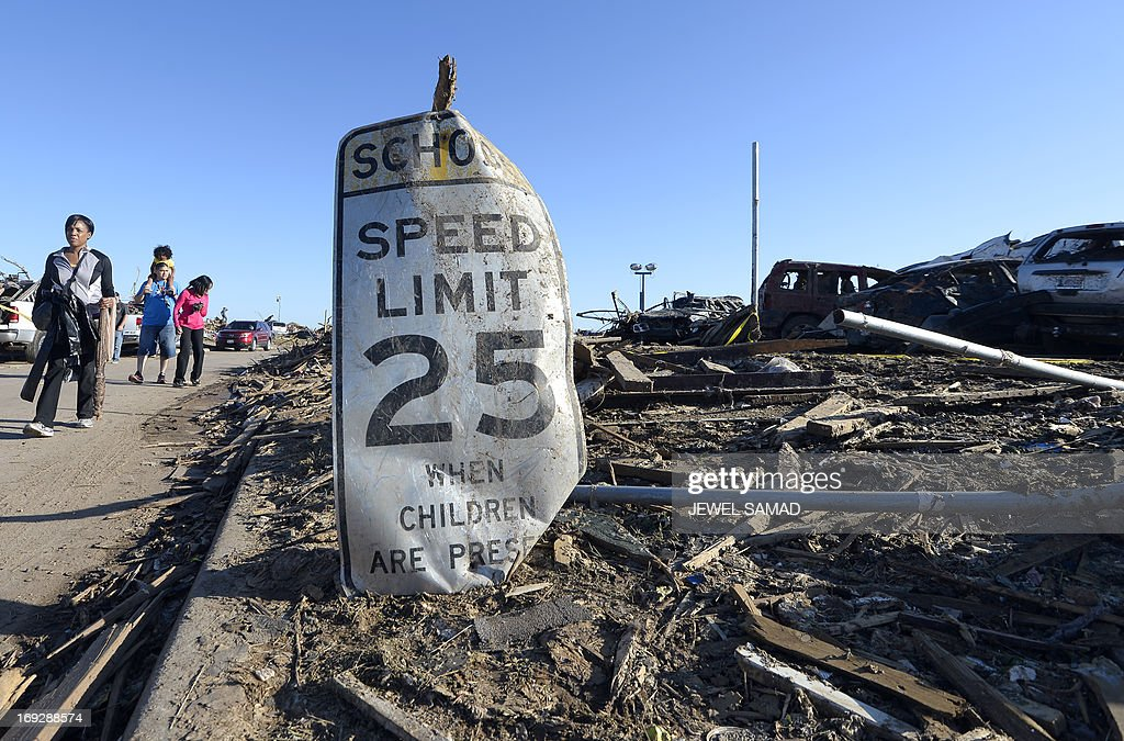 A school zone speed limit sign is kept among the debris outside the Plaza Towers Elementary School after it was destroyed by a tornado that ripped through the area on May 22, 2013 in Moore, Oklahoma. Seven children died in the school during the tornado. As rescue efforts in Oklahoma wound down, residents turned to the daunting task of rebuilding a US heartland community shattered by a vast tornado that killed at least 24 people. The epic twister, two miles (three kilometers) across, flattened block after block of homes as it struck mid-afternoon on May 20, hurling cars through the air, downing power lines and setting off localized fires in a 45-minute rampage. AFP PHOTO/Jewel Samad