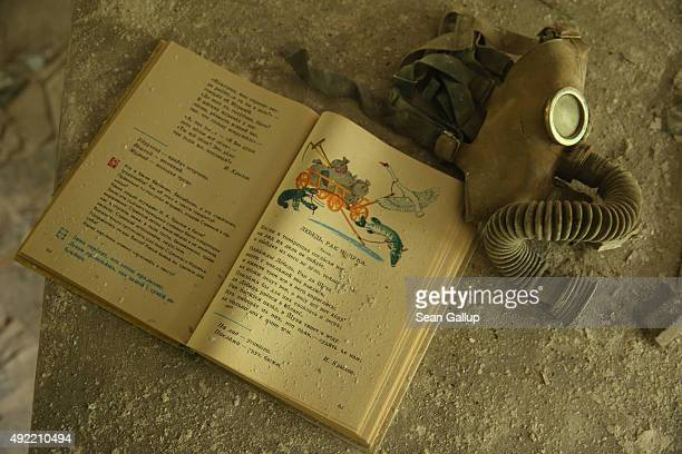 A schoolbook lies on a pupils' desk next to a Cold Warera gas mask in a classroom of abandoned School Number 3 on September 30 2015 in Pripyat...