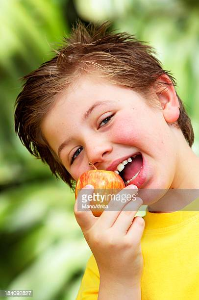 Schoolboy about to eat a crunchy Fiji apple
