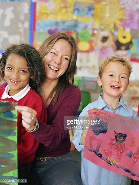 Schoolboy and girl (4-6) either side of teacher, holding paintings