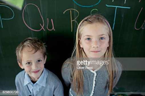 Schoolboy (6-7) and girl (8-9) posing in front of blackboard : Stock Photo