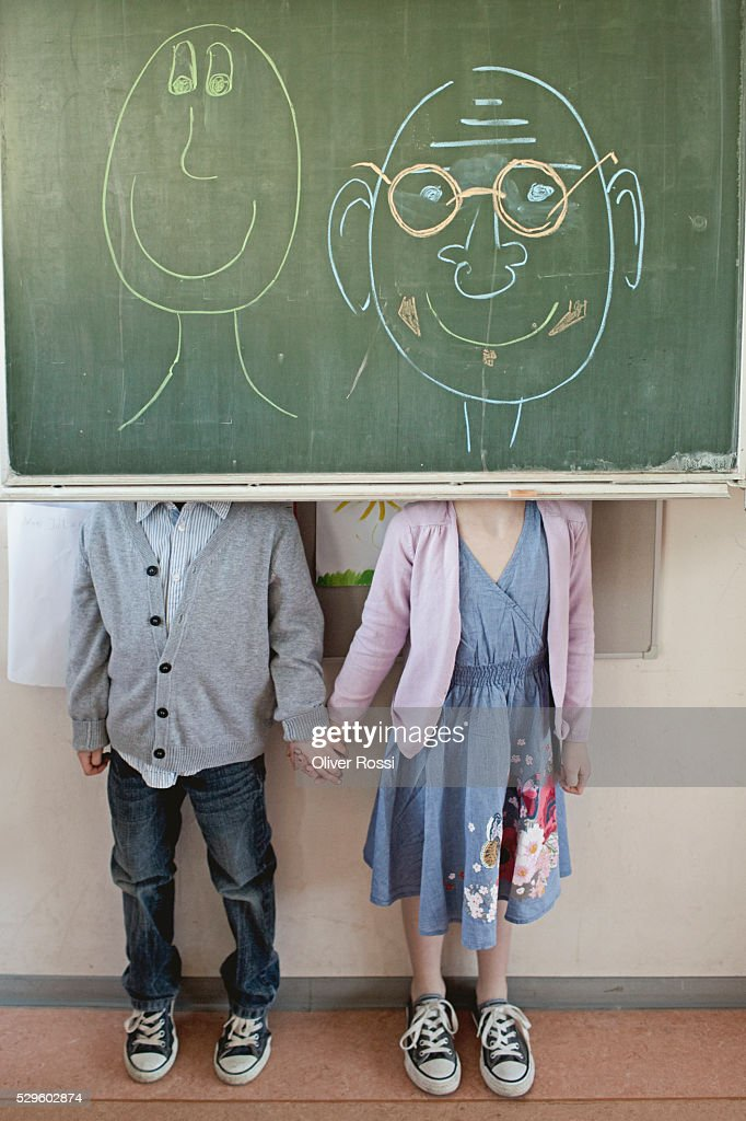 Schoolboy and girl (6-7) standing behind blackboard with adult faces written on it : Foto de stock