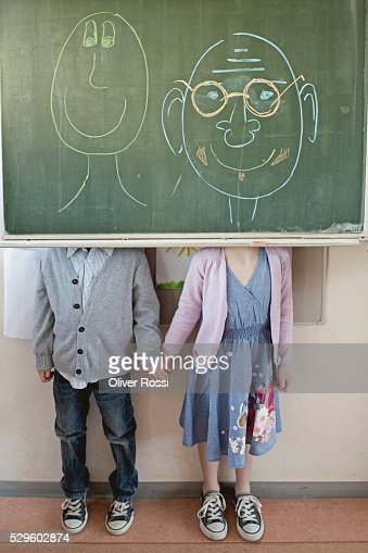 Schoolboy and girl (6-7) standing behind blackboard with adult faces written on it : Stock Photo