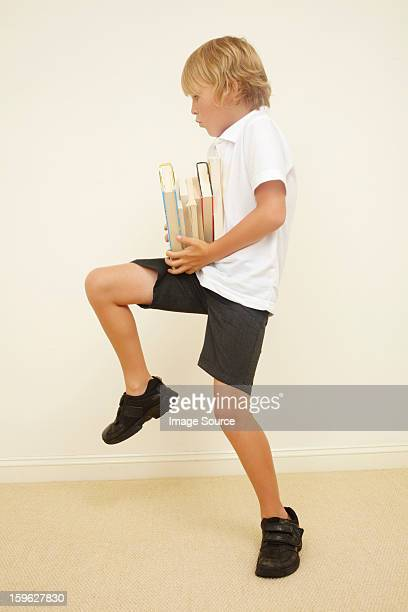 Schoolboy carrying stack of school books