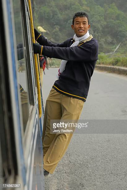 A schoolboy catches a free ride in the doorway of the passenger compartment of the Toy Train as it makes its way uphill through the Himalayan...