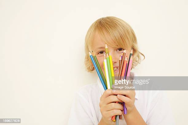 Schoolboy holding bunch of colouring pencils