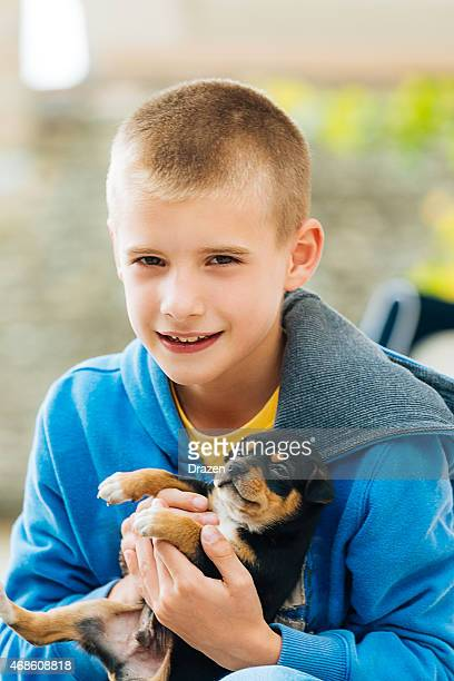 Schoolboy holding his puppy and looking into camera and smiling