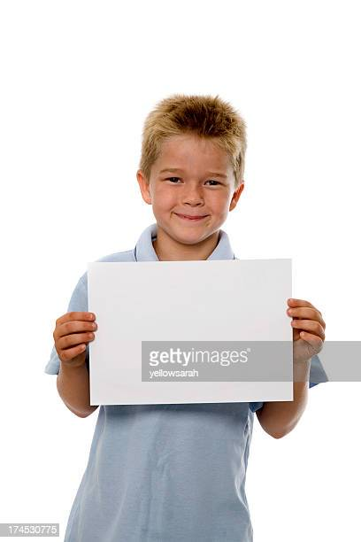 Schoolboy holds white paper with pride
