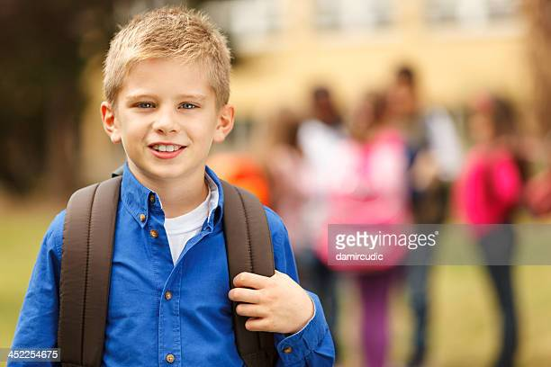 Schoolboy in front of the school