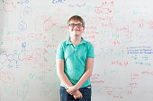 schoolboy in front of wipe board, math equations
