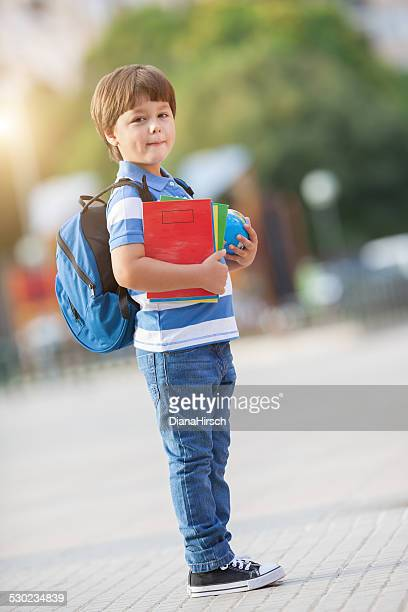 schoolboy in the schoolyard with school supplies