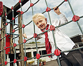 Schoolboy (6-8) looking through climbing net in playground, smiling
