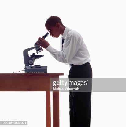 Schoolboy (10-12) looking through microscope, side view : Stock Photo