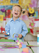 Schoolboy (4-6) making paper chain at table, laughing, portrait