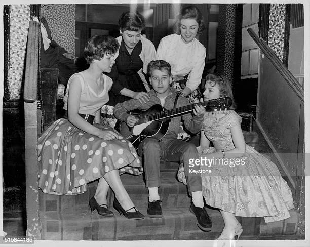 Schoolboy musician Mike Jackson serenading a group of the Vernon Girls during rehearsals for a television show May 15th 1959
