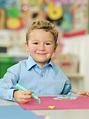 Schoolboy (4-6) painting at table, smiling, portrait