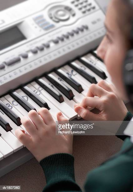 Schoolboy Playing an Electric Piano with the Notes Written onto the Keys