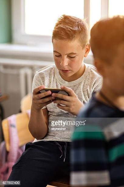 Schoolboy playing games on smart phone during break in classroom.