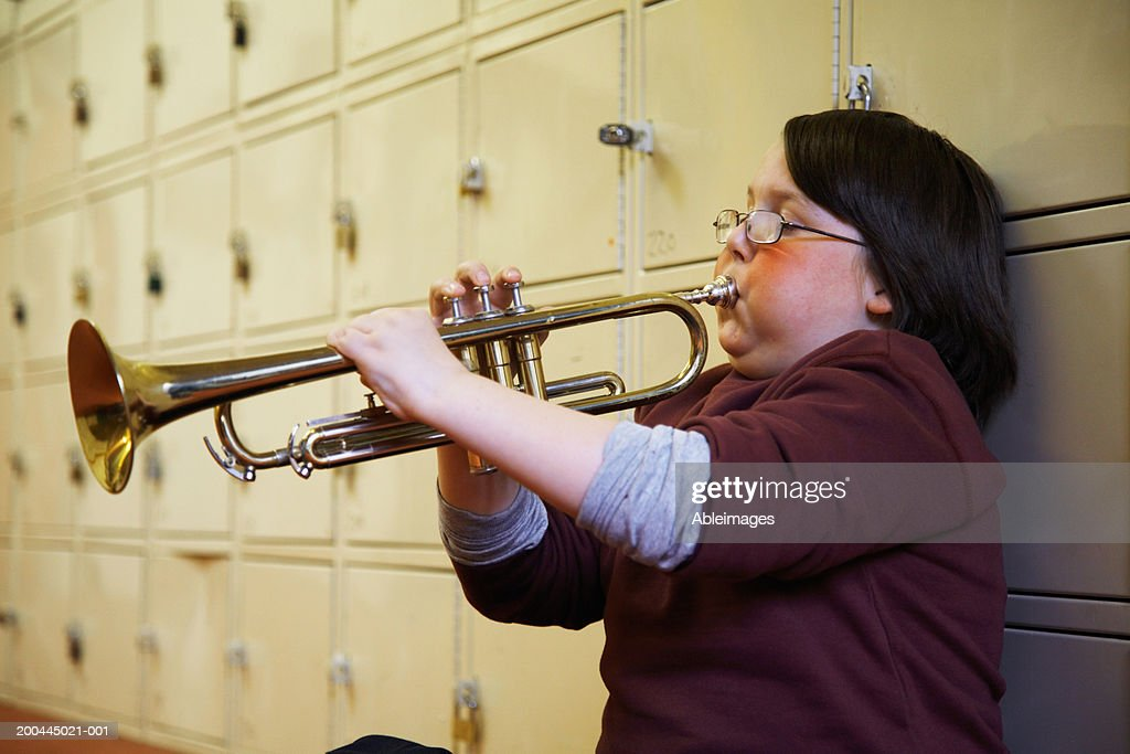 Schoolboy (8-10) playing trumpet, leaning against lockers : Stock Photo