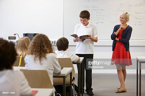 Schoolboy reading from textbook in front of class