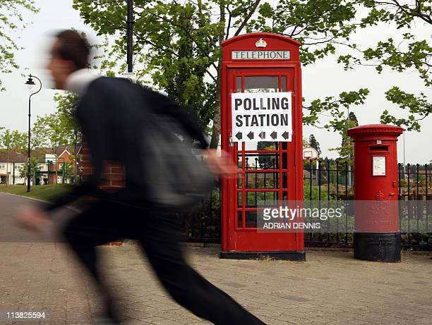 A schoolboy runs past a telephone box close to a community centre doubling as a polling station at Elvetham Heath near Fleet Hampshire on May 5 2011...