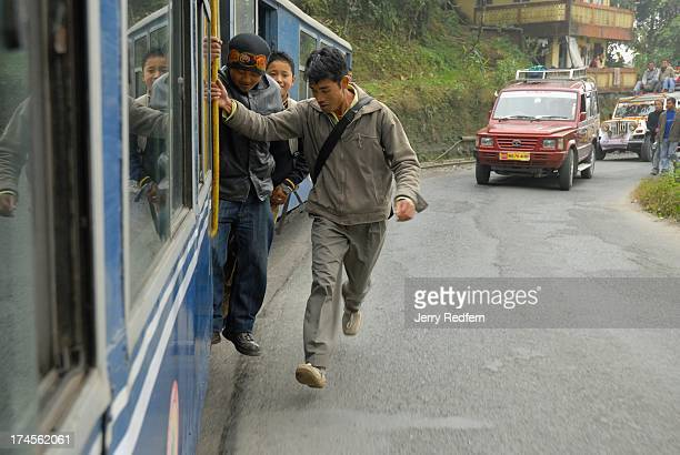 A schoolboy runs to catch a free ride in the doorway of the passenger compartment of the Toy Train as it makes its way uphill through the Himalayan...