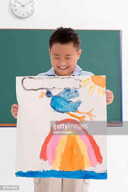 Schoolboy showing his drawing and smiling