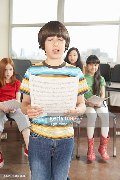 Schoolboy (6-12) singing from music sheet in class