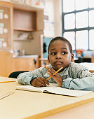 Schoolboy Sits at a Table Daydreaming