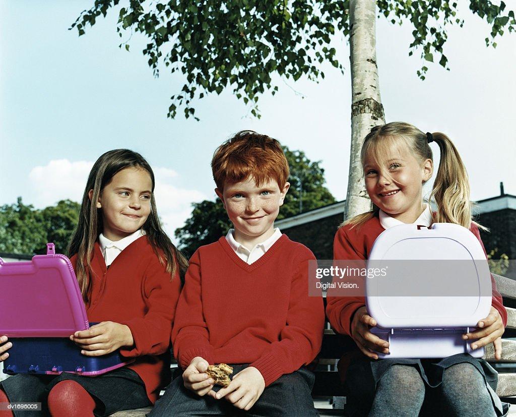 Schoolboy Sitting Between Schoolgirls Eating Their Packed Lunch at School : Stock Photo